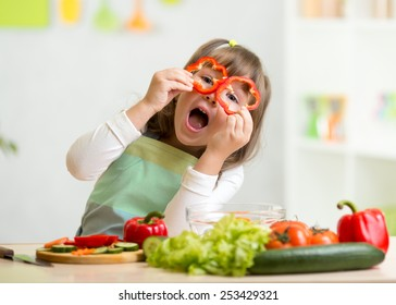 kid girl having fun with food vegetables at kitchen
