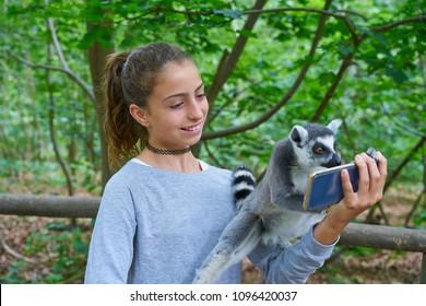Kid girl having fun with ring tailed lemurs selfie photo animals outdoor