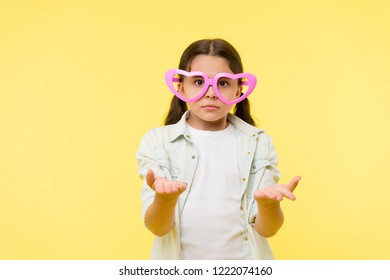 Kid girl heart shaped eyeglasses looks disappointed. Girl wear cute eyeglasses disappointed face. What just happened. She asks you. Child dissapointed confused what going on. Disappointment concept.
