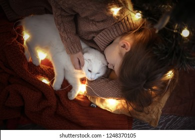 Kid girl hugs and kisses a white domestic cat near the New Year tree, concept cozy and homely Christmas and new year and pets