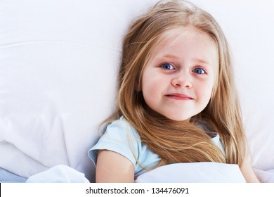 Kid girl lie on bed. Blonde girl