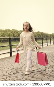 Kid girl with long hair fond of shopping. Fashionista girl with pink bags. Girl likes to buy clothes. Shopping concept. Girl shopping on calm face carries shopping bags, urban background.