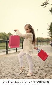 Kid girl with long hair fond of shopping. Fashionista girl shopping with pink bags. Shopping concept. Girl likes to buy clothes. Girl calm face carries shopping bags, urban background.
