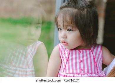 kid girl looking outside on windows