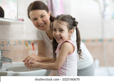 kid girl with mom washing her hands in bathroom