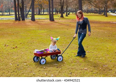 Kid girl and mother walking in the park with pull cart