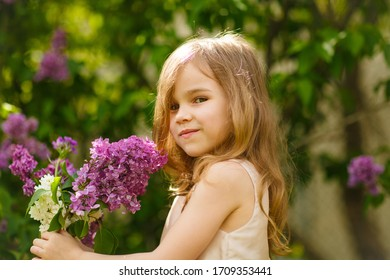kid girl in a pink dress near a bush of lilac flowers with a bouquet in hand. warm spring.