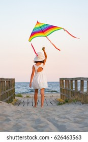 Kid girl play with rainbow triangle kite on the beach at sunset