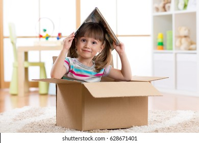 kid girl playing with book in a toy house in children room.