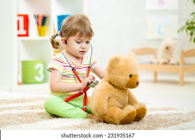 kid girl playing doctor with plush toy at nursery