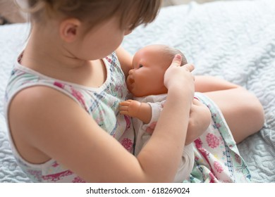 Kid girl playing with a doll, playing in breastfeeding, taking care of a doll, life style and childhood