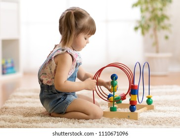 kid girl playing with educational toy indoors