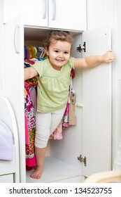 kid girl playing and hiding inside wardrobe