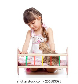 kid girl playing with a kitten and rocking him in doll crib