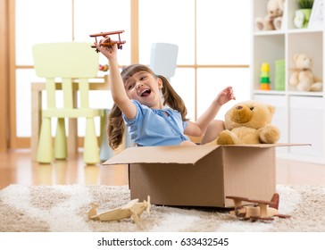 Kid girl playing pilot flying a cardboard box in children room