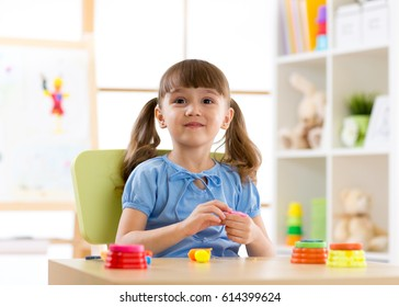 Kid girl playing with plasticine at home or playschool
