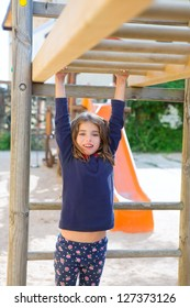 kid girl playing in playground  hanging from wood bars smiling happy