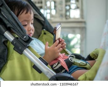 Kid girl playing smartphone lying on stroller