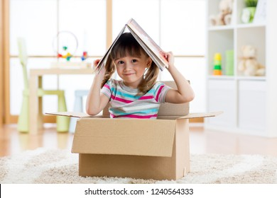 kid girl playing in a toy house in nursery room