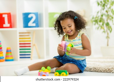 Kid girl playing toys at home or kindergarten
