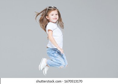 Kid girl preschooler in blue jeans, white t-shirt and sunglasses is jumping isolated on grey background