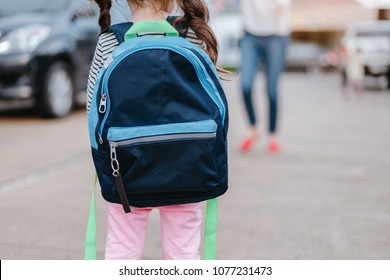 A Kid girl pupil waiting parent or mother get your child back from school.