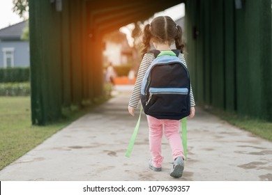 Kid girl pupil walking back to home after learning study school alone with schoolbag,preschool and kindergarten education concept.