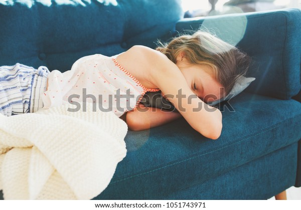 kid girl relaxing at home in weekend morning and sleeping on cozy couch in pajama