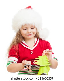 kid girl in Santa Claus hat cutting christmas tree from paper