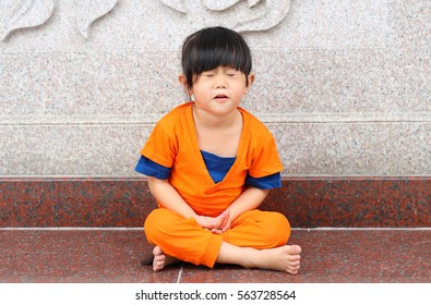 Kid girl in Shaolin monk orange clothes doing Meditation expression in chinese temple in thailand, Chinese new year concept.