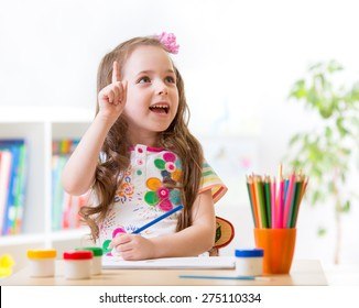 Kid girl showing gesture paints and draws in nursery