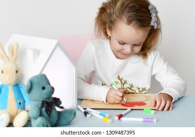 Kid girl sits st the desk and paints picture with multicolored markers accompanied by rabbit and bear