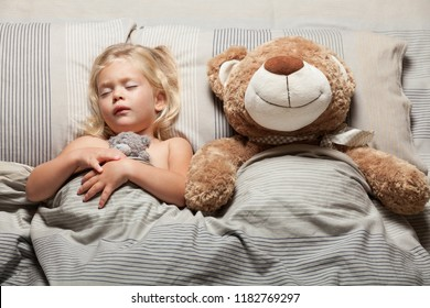Kid girl and teddy bear in bed, nightmare problem. Scared, stress.