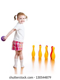 Kid girl throwing ball to knock down toy bowling pins. Focus on child.