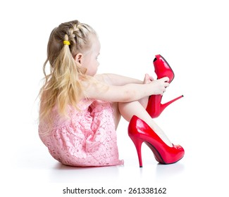 Kid girl trying red mummy shoes on.  Isolated on white