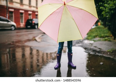 kid girl with umbrella, waterproof coat and boots jumping in puddle and mud in the rain. Kid walking in summer rain