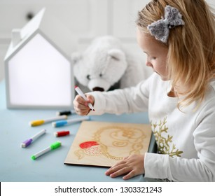 Kid girl in white shirt sits at the desk and paints hedgehog picture with multicolored markers accompanied by white bear