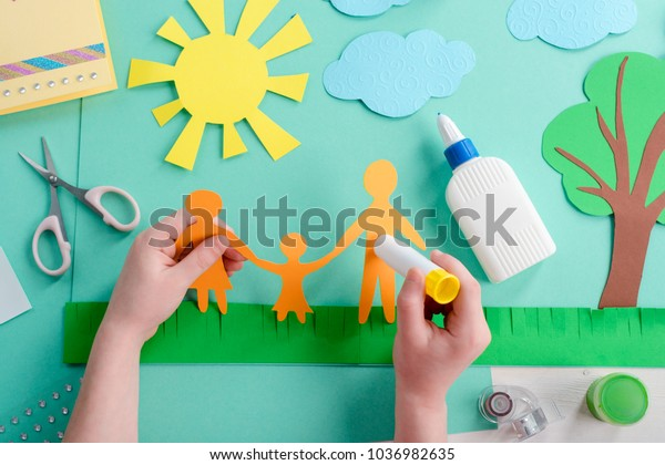 Kid is gluing paper shape on a collage devoted to international family day. Child's creativity, craft classes and ideas.