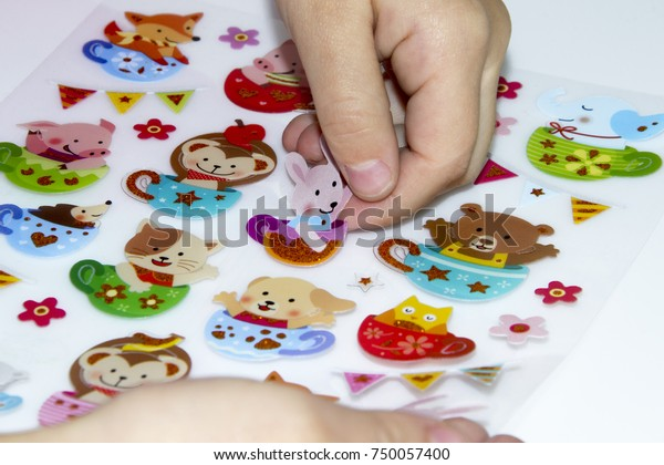 Kid is gluing a sticker on applique