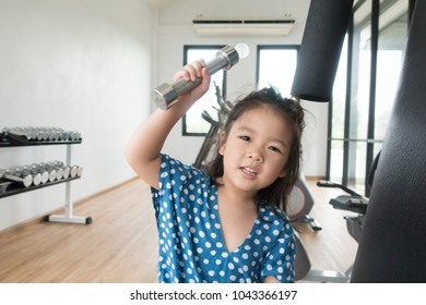 Kid in Gym.Smile Little asian girl training with dumbbells at fitness center.