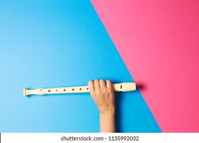 Kid hand with flute on colorful background