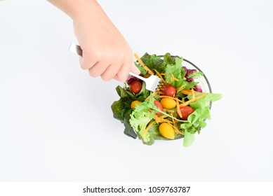Kid hand and and folk take salad from a bowl