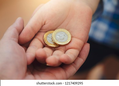 Kid hand giving two pound coin to his mam for donate to poor children,Crop view of children hand giving money coin to another person,Children learning about sharing and giving and donation concept