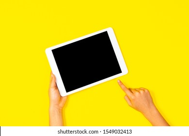 Kid hand holding white tablet computer and pointing to blank screen on yellow background