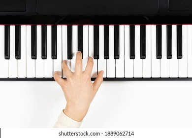 Kid hand learning to play on the piano. Top view