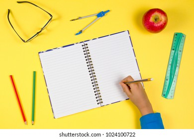 Kid hand with open notebook, pen, ruler, glasses and fresh apple on yellow background