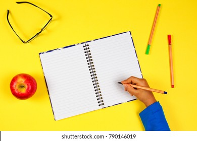 Kid hand with open notebook, pen, glasses and fresh apple on yellow background