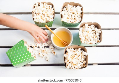 Kid hand taking popcorn from full bowls and honey on white wooden table from top down perspective.