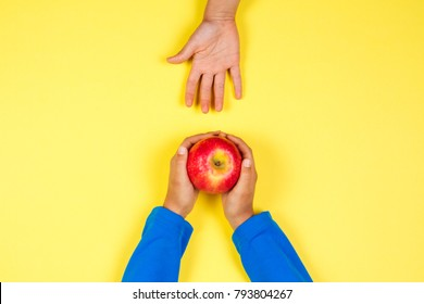 Kid hand taking red apple from another child's hands