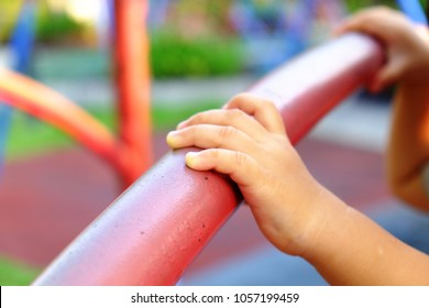 kid hand touch a red bar in evening